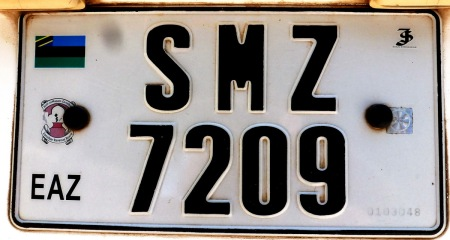 SERIKALI MAPINDUZI ZANZIBAR.  (Swahili for: Revolutionary Government of Zanzibar)         More recent SMZ government plates are being manufactured using the new Utsch equipment, though continuing the 4-numeral serials, as with SMZ 7209.